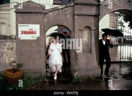 May 1989. Rain speeds up the exit of a bride and groom after a church wedding shortly before the 1989 elections, in a town near Warsaw. Fot. Chris Niedenthal/FORUM - Stock Photo