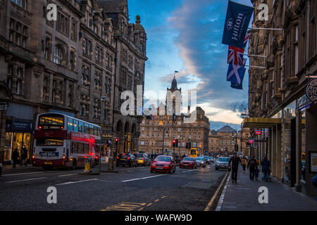 Moody street scene of the Royal Mile Edinburgh Scotland UK showing Hilton hotel, old tall buildings, shops, cars, buses and people plus flags - Stock Photo