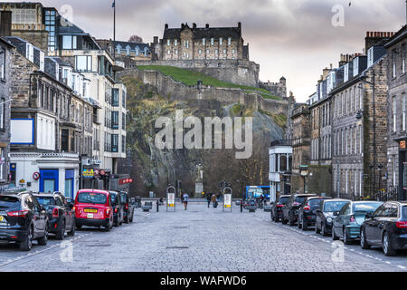 Cobbled street view looking towards the  Statue of Thomas Guthrie on Princes Street with the Castle above Edinburgh Scotland
