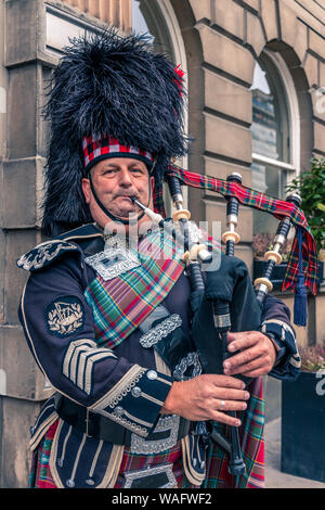 Close up head and shoulders of a Scottish bagpiper playing pipes in full uniform Edinburgh, Scotland - Stock Photo