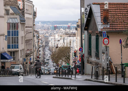Paris, France - January 26, 2019: the Menilmontant Street (rue Menilmontant) at Paris with a bicycle, the 96 bus, a few cars and people walking. It is - Stock Photo