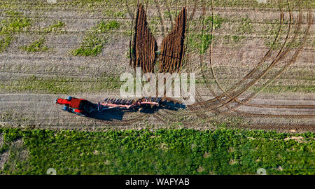 creative tractor driver drew a butterfly on the field aerial view - Stock Photo