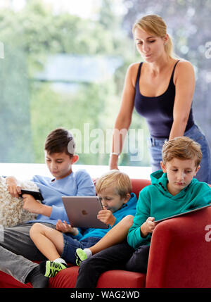 Mother watching over her children using devices - Stock Photo
