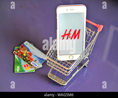 Yaroslavl, Russia - August 20, 2019: Smartphone with H&M logo in shopping cart and credit cards on the table. - Stock Photo