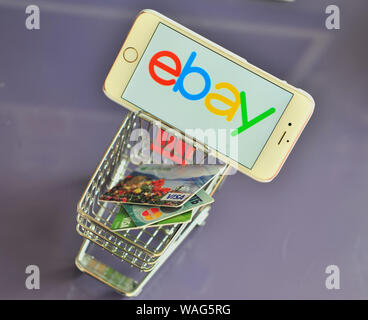 Yaroslavl, Russia - August 20, 2019: Smartphone with ebay logo in shopping cart with credit cards. - Stock Photo