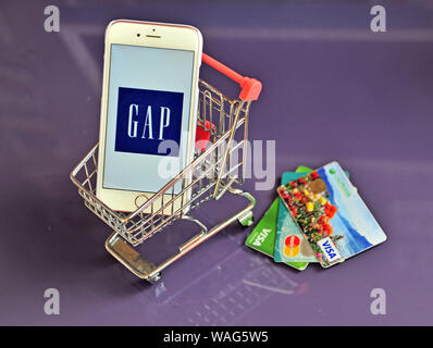 Yaroslavl, Russia - August 20, 2019: Smartphone with Gap logo in shopping cart on the table. - Stock Photo