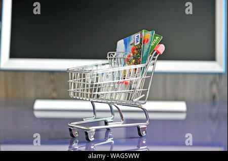 Yaroslavl, Russia - August 20, 2019: Mini shopping trolley with credit cards on the table. - Stock Photo