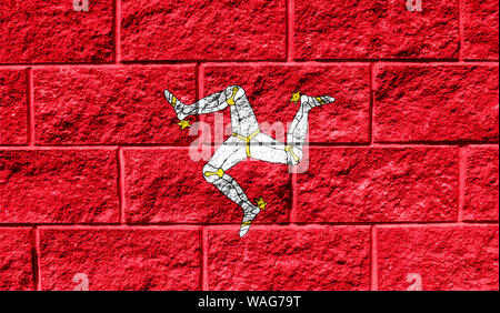 Flag of Isle Of Man close up painted on a cracked wall - Stock Photo