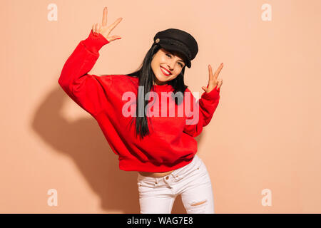 Young smiling girl wearing black cap and red hoodie over isolated background looking to the camera showing fingers doing victory sign. Number two. - Stock Photo