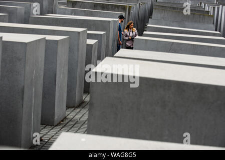 August 16, 2019, Berlin, Germany: Visitors walk through hundreds of concrete slabs or ''stelae'' part of the Memorial to the Murdered Jews of Europe or ''Holocaust Memorial'' located south of the Brandenburg Gate. Holocaust Memorial was designed by American architect Peter Eisenman occupying an area of 19,000-square-metre covered by 2711 concrete slabs or ''stelae' (Credit Image: © Omar Marques/SOPA Images via ZUMA Wire) - Stock Photo