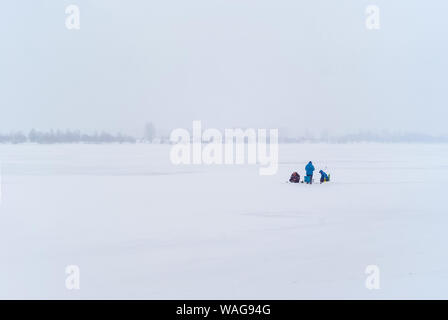 three fishermen in the distance do ice fishing in a foggy snowy winter landscape - Stock Photo