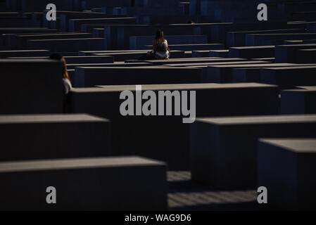 August 19, 2019, Berlin, Germany: Visitors walk through hundreds of concrete slabs or ''stelae'' part of the Memorial to the Murdered Jews of Europe or ''Holocaust Memorial'' located south of the Brandenburg Gate. Holocaust Memorial was designed by American architect Peter Eisenman occupying an area of 19,000-square-metre covered by 2711 concrete slabs or ''stelae' (Credit Image: © Omar Marques/SOPA Images via ZUMA Wire) - Stock Photo