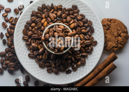 White Coffee cup with roasted coffee beans, cinnamon and biscuits on isolated white background from above. Coffee beans on plate and in the mug. - Stock Photo