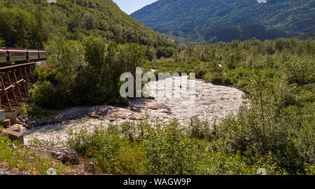 a tourist train on the white pass route crosses over a river running through a mixed forest near skagway alaska - Stock Photo