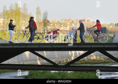 Some people crossing a bridge over Manzanares river in Madrid. - Stock Photo
