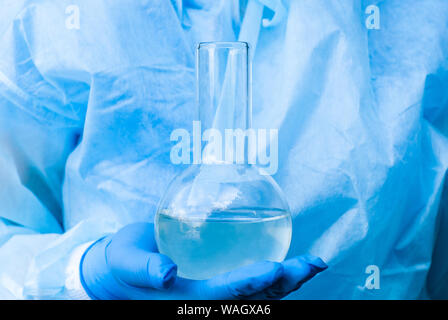 researcher's hand in a glove holds a glass laboratory flask with liquid, background in blue tones - Stock Photo