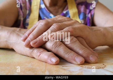 Close-up of a senior woman's hands put together on a kitchen table. Old lady wearing colorful pinafore, selective focus, natural lighting, front view.