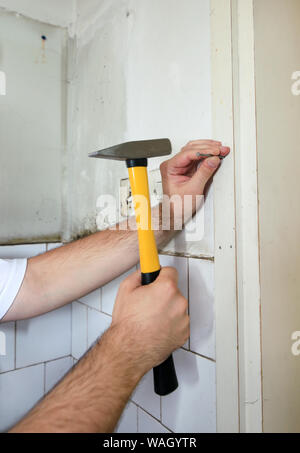 Construction worker and handyman working on renovation work. Builder with yellow hammer strikes and nails a nail into wooden wall of kitchen door.