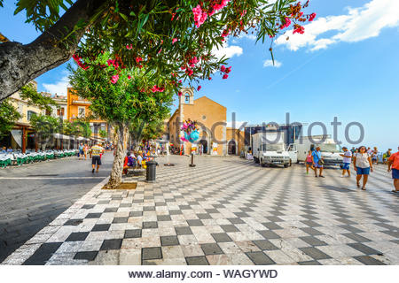 Tourists and locals mingle on the busy Piazza Aprile just off the main Corso Umberto road on the island of Sicily in the resort town of Taormina Italy - Stock Photo