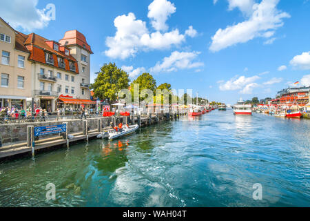 Tourists enjoy shops, boats and cafes on the boardwalk at Alter Strom canal in the town of Warnemunde, Rostock on the northern coast of Germany - Stock Photo