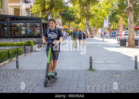ISTANBUL, TURKEY - AUGUST 5, 2019: Peoples are walking and Young boy riding on electric kick scooter. E - Kick - Scooter by 'MARTI Tech', the Turkish - Stock Photo