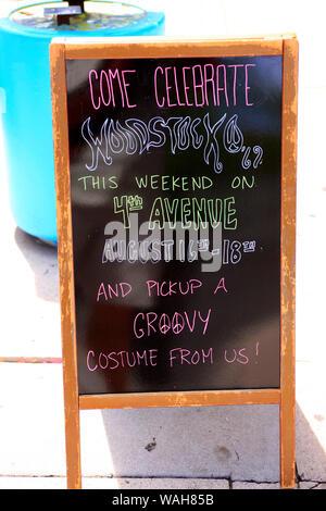 Sidewalk store sign - Lets celebrate Woodstock on 4th Avenue seen in Tucson AZ - Stock Photo
