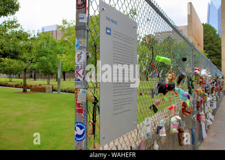 The memorial fence at Oklahoma City National Memorial is shown at an angle with one of the time gates and chairs in the background. - Stock Photo