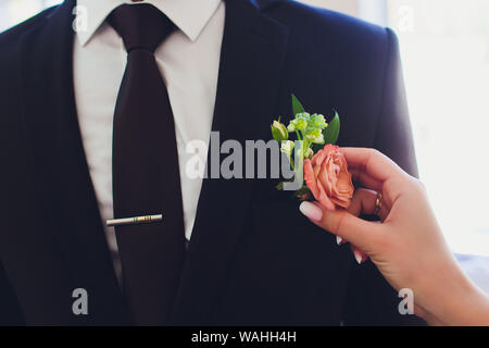 Boutonniere in form of rose on wedding suit of groom. - Stock Photo