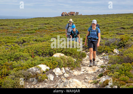 Hiking on the Kangaroo Island Wilderness Trail, with the Remarkable Rocks behind - Stock Photo