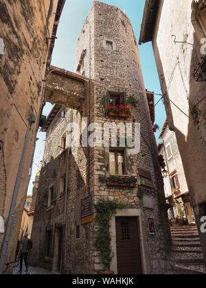 A narrow stone paved street and old medieval houses with arched wooden doors also metal curtains on the windows in small ancient town Sermoneta, Italy - Stock Photo