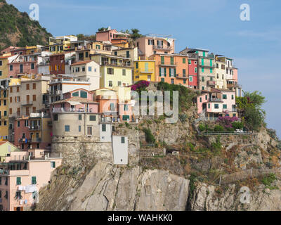 View of Manarola. Colorful historic buildings on a steep cliff close up. Italian cityscape. Cinque Terre area is a popular tourist destination. Italy. - Stock Photo