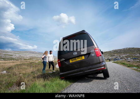 Tourists analyze the situation after their car rental went off a narrow road in Harris, Lewis Island, Outer Hebrides, Scotland, UK - Stock Photo