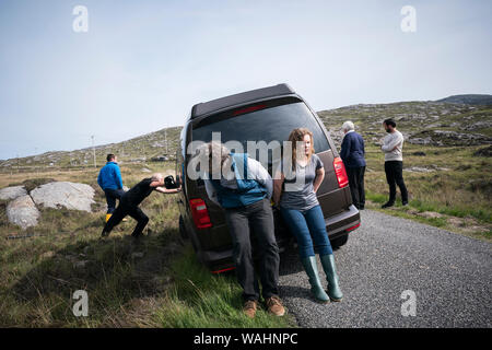Man and teenage girl push the back end of a car rental stuck in the ditch as other tourists watch from the sidelines as another adult man pushes the f - Stock Photo