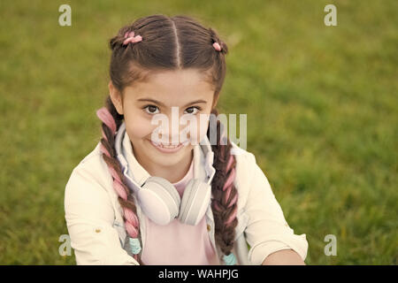 Look on bright side. Secrets to raising happy child. Girl cute kid green grass background. Healthy emotional happy kid relaxing outdoors. Get happy yourself. Girl modern headphones enjoy relax. - Stock Photo