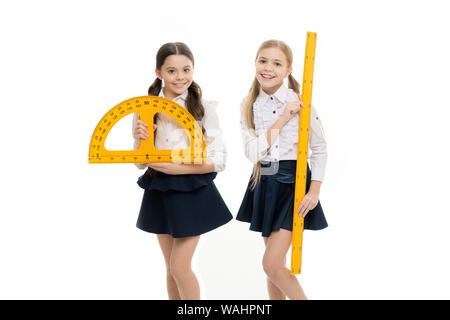 An important lesson. Little girls preparing for geometry lesson. Cute schoolgirls with measuring instruments at school lesson. Small children holding protractor and ruler for lesson. - Stock Photo