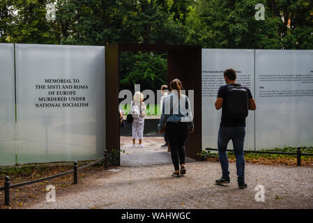 Visitors at the Memorial to the Sinti and Roma Victims of Europe Murdered Under National Socialism next to the Germany's Parliament Building. The Memorial was designed by Dani Karavan. - Stock Photo