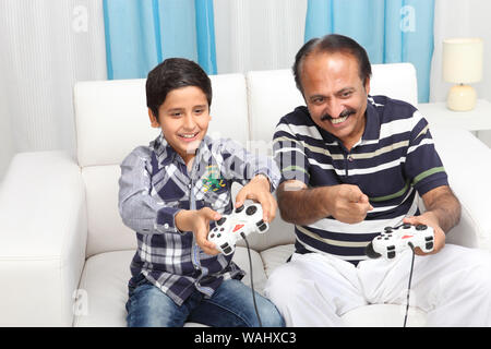 Indian old man with his grandson playing video game at home - Stock Photo