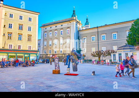 SALZBURG, AUSTRIA - FEBRUARY 27, 2019: Street performance of the living statue mime artist, standing on the air amid the Alter Markt (Old Market) squa - Stock Photo