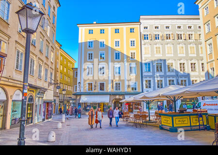 SALZBURG, AUSTRIA - FEBRUARY 27, 2019: The narrow Alter Markt square in old town is the center of tourist leisure with numerous cafes, restaurants and - Stock Photo