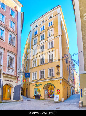 SALZBURG, AUSTRIA - FEBRUARY 27, 2019: The high residential house with shop in the ground floor located in tiny medieval Goldgasse street of Altstadt - Stock Photo