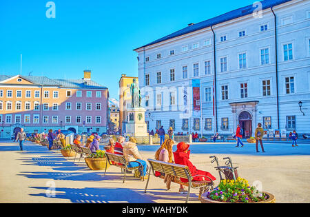 SALZBURG, AUSTRIA - FEBRUARY 27, 2019: The line of benches in Mozartplatz next to the Mozart monument with a view on the walls of Salzburg Museum is a - Stock Photo