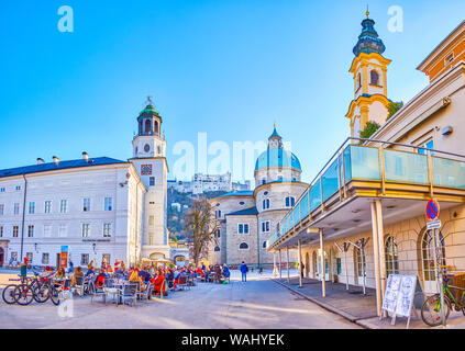 SALZBURG, AUSTRIA - FEBRUARY 27, 2019: The scenic outdoor cafe in Mozartplatz among famous landmarks of old town is a fine place to have a short brake - Stock Photo