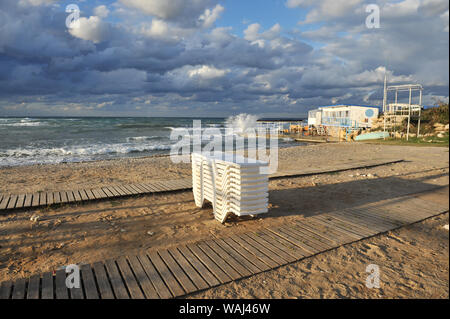 out off season resort sea beach at warm sunset with deckchairs and lounger on sand - Stock Photo