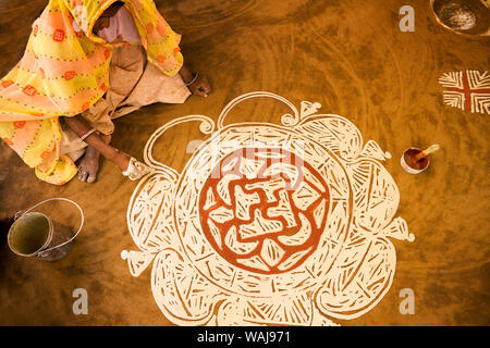 India, Rajasthan, Nawalgarh. Woman painting Diwali rangoli design on floor. Credit as: Jim Nilsen / Jaynes Gallery / DanitaDelimont.com - Stock Photo