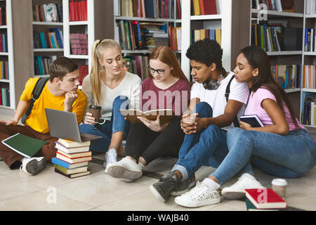 Group of diverse students sitting on floor at library - Stock Photo