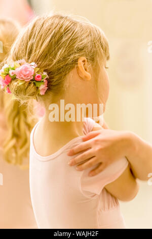 Rear view portrait of a six year old girl ballet dancer hugging herself, who is wearing a floral ballet bun hairpiece, in a dance studio. (MR) - Stock Photo