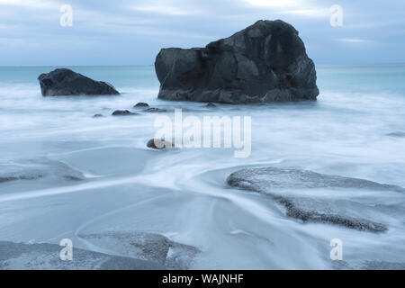 Norway, Lofoten Islands, Vestvag Island, Leknes. Here on the western side of Vestvag Island, the dark rocks contrast with the white water. - Stock Photo