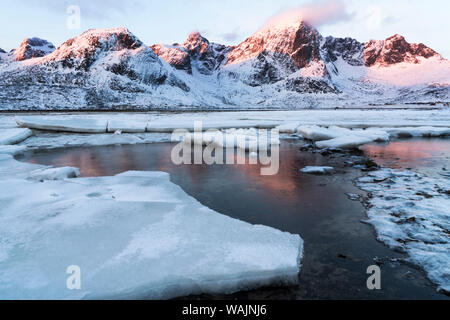 Norway, Lofoten Islands, Vestvag Island. Ice slabs along the coast are broken up by the tide fluctuations. - Stock Photo
