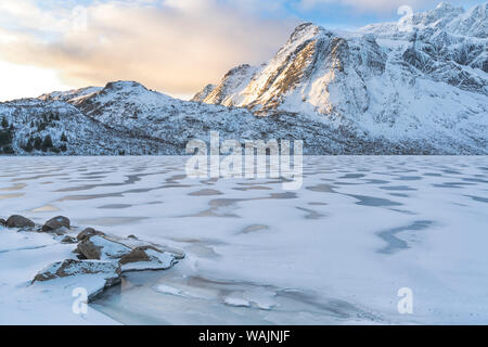 Norway, Lofoten Islands, Vestvag Island, Leknes. Wind has blown snow into patterns on the surface of a frozen lake. - Stock Photo