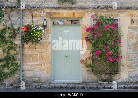 Cotswold stone town house with pink climbing roses and a hanging basket in the market place of Stow on the Wold, Cotswolds, Oxfordshire, England - Stock Photo